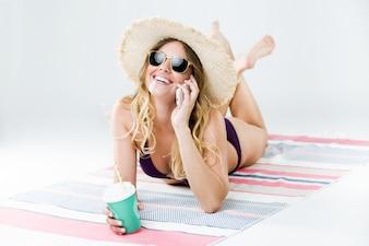 Mulher rindo enquanto falava no telefone com óculos de sol