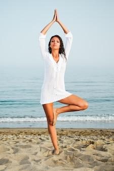 Mulher saudável que faz a ioga na praia