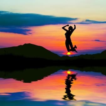 Mulher saudável que salta com fundo do sol