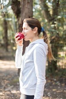 Mulher saudável que morde uma maçã