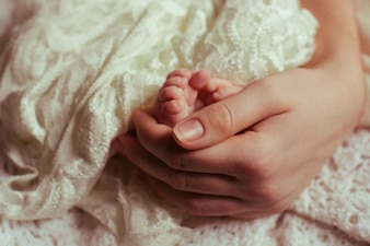 Mulher, segurando os pés do bebê