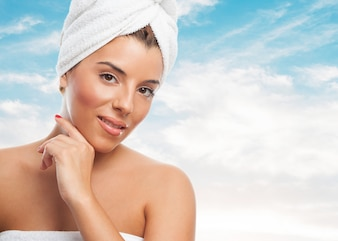 Mulher sensual na toalha branca sobre o céu azul.
