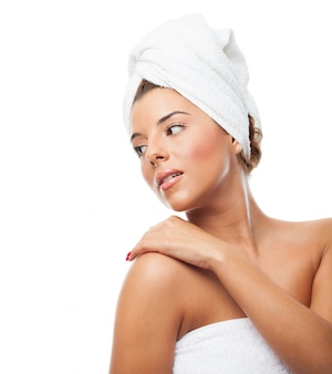 Mulher sensual na toalha que olha por cima do ombro