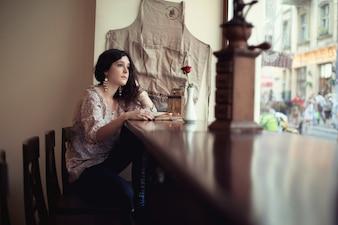 Mulher sentada em uma mesa de madeira