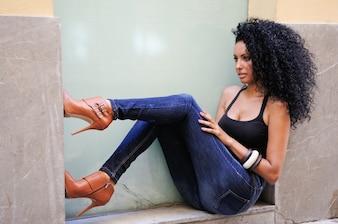 Mulher sentada em uma vitrine com os pés na parede