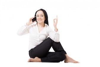 Mulher sentada no chão falando em seu telefone
