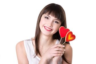 Mulher sorridente com biscoitos em forma de coração