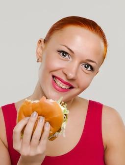 Mulher sorridente com hambúrguer