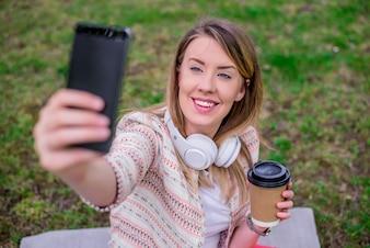 Mulher sorridente feliz sentada na grama e faz auto-retrato no smartphone. Mulher, mão, segurando, papel, copo, café, ao ar livre. Retrato de mulher sorridente no parque e fazendo um selfie engraçado, olhando a câmera.