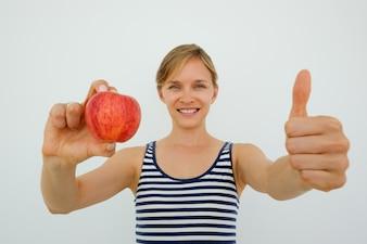 Mulher sorridente mostrando maçã e polegar para cima