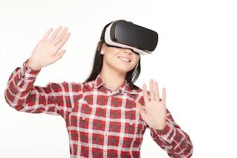 Mulher sorridente no fone de ouvido VR tocando o ar pelas mãos.