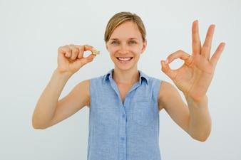 Mulher sorridente segurando moedas e mostrando sinal OK