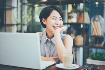 Mulher sorrindo com um café e um laptop