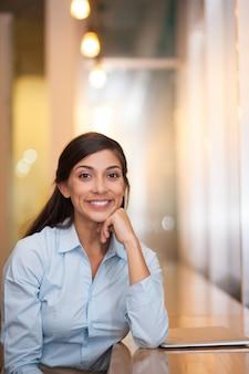 Mulher sorrindo sentado no café com portátil fechado