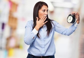 Mulher surpreendida que olha um despertador
