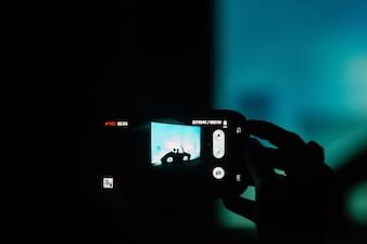 Mulher tira uma foto de silhuetas na parede