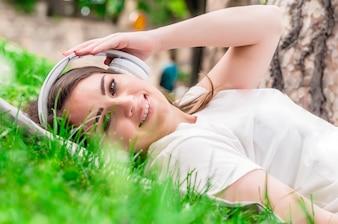 Mulher tranquila ouvindo música com fones de ouvido ao ar livre
