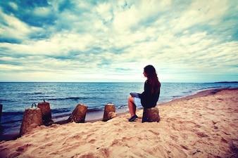 Mulher triste e solitária sentada na praia.