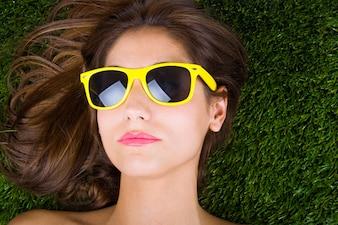 Mulher tumbada sobre a hierba com gafas de sol