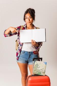 Mulher turística apontando para o livro em branco