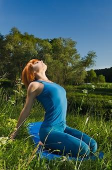 Mulher vermelha praticando fitness yoga ao ar livre