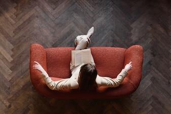 Mulher visto de cima lendo um livro