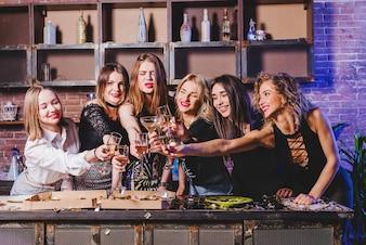 Mulheres amigas tilintando óculos