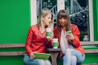 Mulheres com copos de café que olham um telemóvel