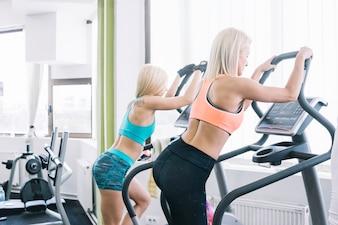 Mulheres em roupas esportivas usando máquina de passo