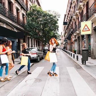 Mulheres jovens que cruzam a estrada