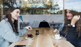 Mulheres novas bonitas que bebem o chá em uma cafetaria.