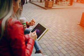 Mulheres que tocam em um tablet