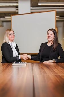 Mulheres sentadas à mesa apertando as mãos, sorrindo
