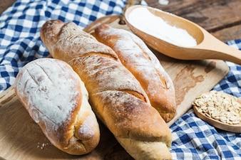 Naco de pão colocado sobre uma placa de madeira e uma toalha de mesa