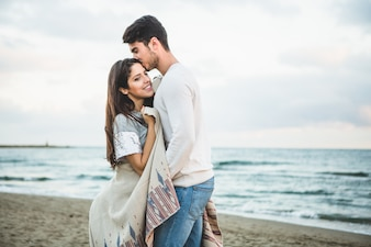Namorado beijando sua namorada na testa em uma praia