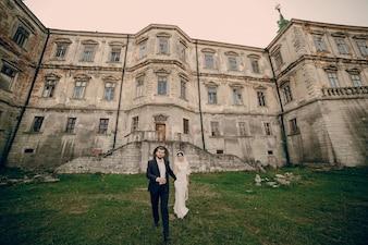 Newlyweds na frente de uma grande casa