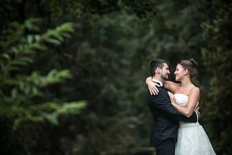 Newlyweds olhando em seus olhos com uma floresta no fundo