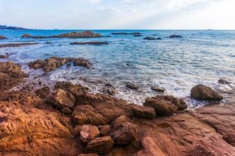 Ninguém lindo a pedra do mar relaxa nuvens