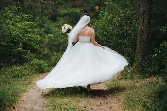 Noiva e noivo com um buquê de flores vermelhas e verdes na mão