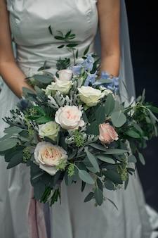 Noiva segura grande bouquet de casamento feito de vegetação e rosas brancas