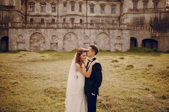 Noivo beijando a testa de sua mulher com fundo do edifício de pedra