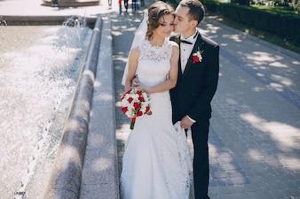 Noivo feliz beijando a bochecha de noiva