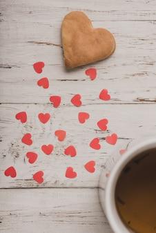 O biscoito com corações vermelhos e um copo