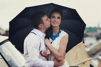 O casal sonhador levanta sob o guarda-chuva no telhado
