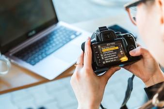 O fotógrafo altera as configurações de sua câmera DSLR no escritório moderno