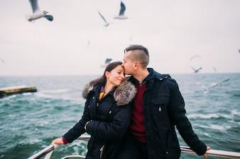 O homem beijando uma mulher na testa com pássaros fundo