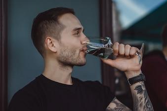 O homem tatuado bonito em um terraço de verão em um café da cidade está bebendo vinho. Street Cafe.