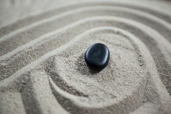 O jardim do zen com areia ajuntada e pedra