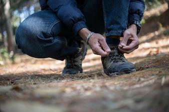O jovem caminhante amarra os laços no sapato durante uma viagem de férias na floresta.