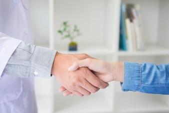 O médico aperta as mãos no consultório médico com paciente, usando óculos, estetoscópio e bata de laboratório.